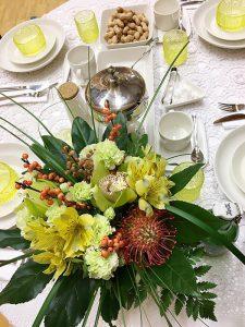 Juhlapöydän päädyssä voi olla korkeampi kukka-asetelma